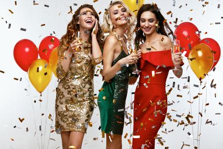 Mujeres hermosas que celebran el Año Nuevo, divirtiéndose en la fiesta. Retrato de las niñas sonrientes felices en elegantes vestidos glamorosos con Champagne Glasses en el partido de la moda. Alta resolución.