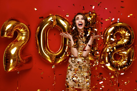 New Year. Woman With Balloons Celebrating At Party. Portrait Of Beautiful Smiling Girl In Shiny Golden Dress Throwing Confetti, Having Fun With Gold 2018 Balloons On Background. High Resolution.