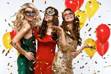 Holiday. Beautiful Women In Masks Celebrating New Year. Portrait Of Happy Girls In Festive Carnival Masks And Stylish Colorful Dresses Having Fun At Party. High Resolution. Фото со стока