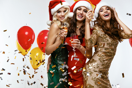 Sexy Smiling Young Women Dressed In Santa Hats And Fashionable Bright Dresses Holding Champagne Glasses At Celebration Stock Photo