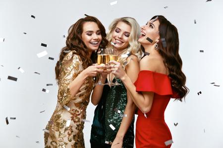 Mooie vrouwen vieren Nieuwjaar, plezier op feestje. Portret van gelukkig lachende meisjes In stijlvolle glamoureuze jurken met champagneglazen op Fashion Party. Hoge resolutie. Stockfoto