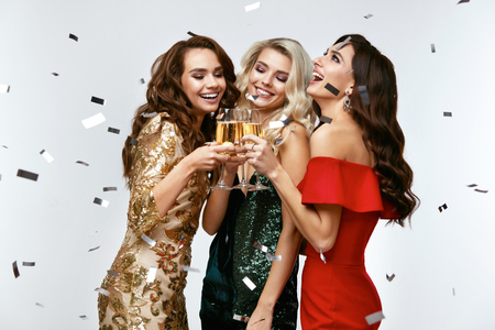 Beautiful Women Celebrating New Year, Having Fun At Party. Portrait Of Happy Smiling Girls In Stylish Glamorous Dresses With Champagne Glasses At Fashion Party. High Resolution.