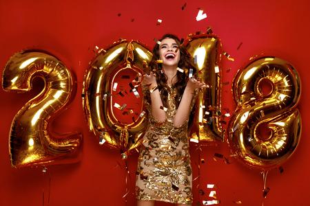 Nieuwjaar. Vrouw met ballonnen vieren op feestje. Portret van mooi glimlachend meisje in glanzende gouden jurk gooien Confetti, plezier met goud 2018 ballonnen op achtergrond. Hoge resolutie.