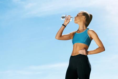 女性実行した後水を飲む。青い空を背景にボトルから水のフィットネス トレーニング、飲み後に明るいカラフルなスポーツウェアが安静時のスポー