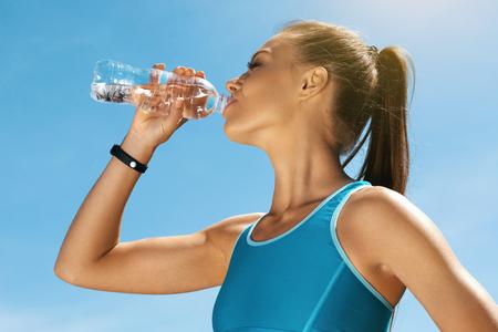 Femme de l'eau potable après la course. Portrait de la belle fille athlétique en vêtements de sport colorés lumineux au repos après la séance d'entraînement de remise en forme, boire de l'eau de la bouteille sur fond de ciel bleu. Image de haute qualité