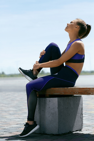 Leg Injury. Woman Suffering From Pain In Leg After Workout. Beautiful Girl In Sportswear Sitting And Touching Painful Ankle Injured While Training Outdoors. Sports Injury. High Resolution