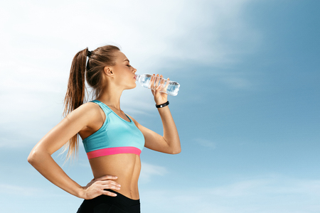 Woman Drinking Water After Running. Portrait Of Beautiful Athletic Girl In Bright Colorful Sportswear Resting After Fitness Workout, Drink Water From Bottle On Blue Sky Background. High Quality Image