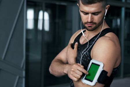 Sport and Music. Man Listening Music On Phone After Workout. Portrait Of Athletic Male With Fit Body Wearing Handphones And Phone In Armband Case. Sport Devices. High Resolution. Stock Photo