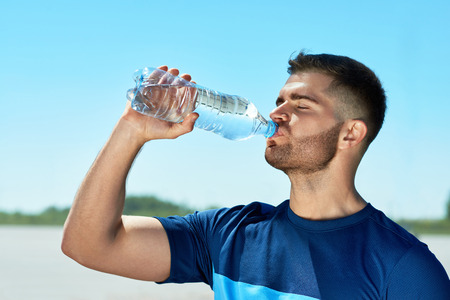 走った後に水を飲む男。フィットネスワークアウト後に休息カラフルなスポーツウェアでハンサムな運動男性の肖像画,青空の背景にボトルから水を