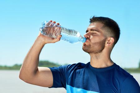 실행 후 마시는 물 남자. 피트 니스 운동 후 쉬고 다채로운 스포츠에서 잘 생긴 체육 남성의 초상화 푸른 하늘 배경에 병에서 물을 마셔. 고품질 이미지