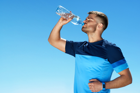 Man Drinking Water After Running. Portrait Of Handsome Athletic Male In Colorful Sportswear Resting After Fitness Workout, Drink Water From Bottle On Blue Sky Background. Stock Photo