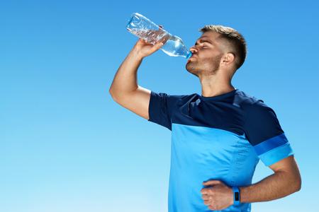 Mann Trinkwasser nach dem Ausführen. Porträt des hübschen athletischen Mannes in der bunten Sportkleidung, die nach Eignungs-Training, Getränk-Wasser von der Flasche auf blauer Himmel-Hintergrund stillsteht.