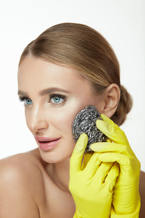 Woman Cleaning Face Skin. Portrait Of Beautiful Smiling Young Female Peeling Facial Skin With Steel Wool Brush. Closeup Attractive Girl In Yellow Gloves Using Abrasive On Facial Skin. High Resolution