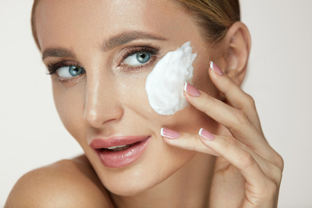 Woman Face Skin Care. Beautiful Smiling Young Female Model Applying Face Wash, Cleansing Beauty Cosmetics On Soft Clean Skin. Closeup Girl With Natural Makeup And Facial Cleanser Foam. High Resolution
