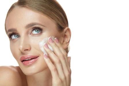 フェイシャルスキンクレンザー。柔らかい健康な肌に泡石鹸を塗るポートレート魅力的な笑顔の女の子。美容化粧品を使用したナチュラルメイク洗