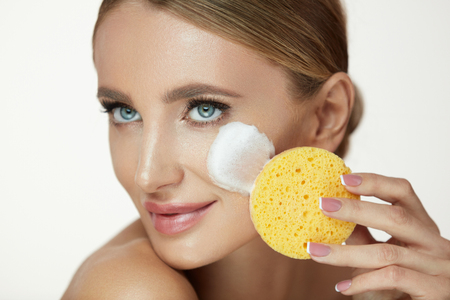 Beauty Face Care. Closeup Smiling Young Woman Using Washing Foam Cleanser And Sponge To Remove Makeup. Portrait Of Beautiful Girl Cleaning Fresh Skin With Face Wash Cosmetic Products. High Resolution