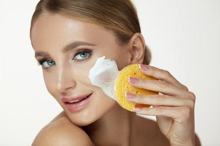 美容フェイスケア。化粧を削除する洗浄フォーム クレンザーとスポンジを使用して若い女性を笑顔をクローズ アップ。洗顔化粧品で新鮮な皮膚を洗