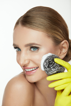 Woman Cleaning Face Skin. Portrait Of Beautiful Smiling Young Female Peeling Facial Skin With Steel Wool Brush And Soap Foam. Closeup Of Attractive Girl Using Abrasive On Facial Skin. High Resolution