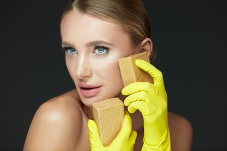 肌を浄化します。洗濯石鹸で顔を洗う手袋で魅力的なセクシーな女の子の肖像画。クローズ アップ美しい若い女性のきれいな柔らかい肌と自然なメ