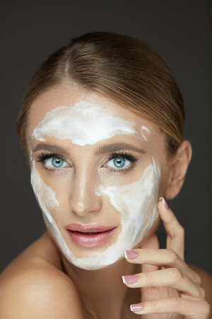 美容化粧品。若い顔に泡を洗って美しい健康な女性モデルの肖像。肌に白いクレンジングマスクを持つ魅力的なセクシーな女性のクローズアップ、