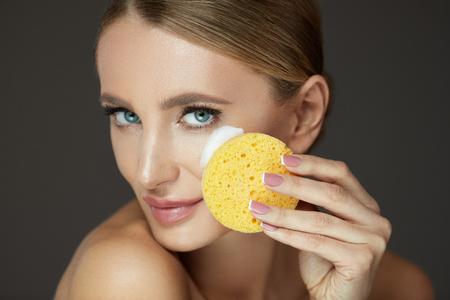 美容フェイスケア。メイクアップを除去するために洗濯フォームクレンザーとスポンジを使用して笑顔の若い女性をクローズアップ。洗顔化粧品で