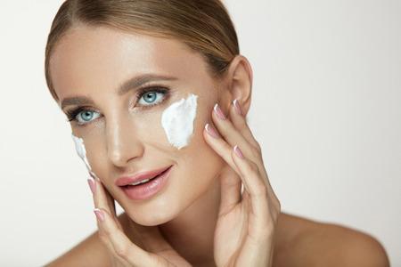 美容スキンケア。フォームフェイスクレンザーでナチュラルメイクで顔の肌をクリーンアップするクローズアップセクシーな女性。顔に白い泡洗浄 写真素材