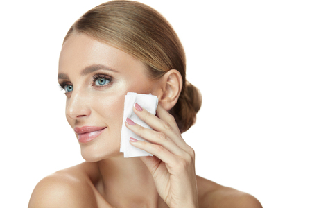 Gezichtsverzorging. Portret van aantrekkelijke glimlachende jonge vrouw make-up verwijderen met natte doekjes. Close-up Mooi Gelukkig Meisje met Natuurlijke Make-up die Gezonde Zachte Huid schoonmaken. Schoonheid Cosmetica. Hoge resolutie