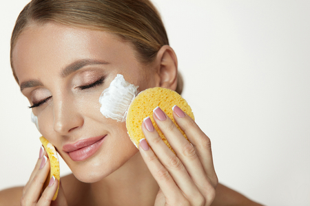 Beauty Face Cosmetics. Portrait Of Beautiful Smiling Girl Cleaning Healthy Clean Fresh Skin With Facial Foam Wash. Closeup Attractive Young Woman Removing Makeup With Cleanser Sponge. High Resolution Stock Photo
