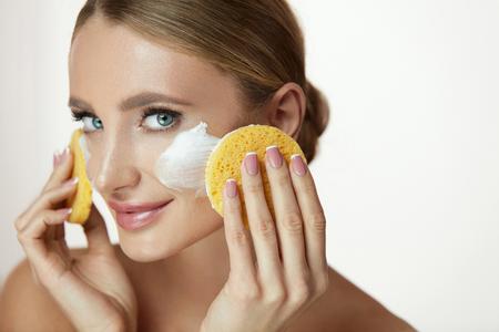 フェイススキンケア。自然なメイクでセクシーな笑顔の若い女性モデルのクローズアップフェイスウォッシュフォーム、化粧品スポンジ付き石鹸。