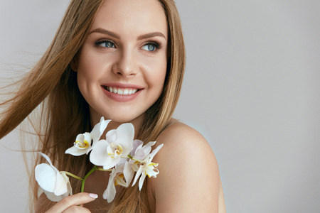 Beautiful Smiling Woman With Flowers. Portrait Of Healthy Happy Girl With Natural Long Blonde Hair, Fresh Clean Face Skin And Perfect White Smile Holding Orchids Indoors. High Quality Image Stock Photo