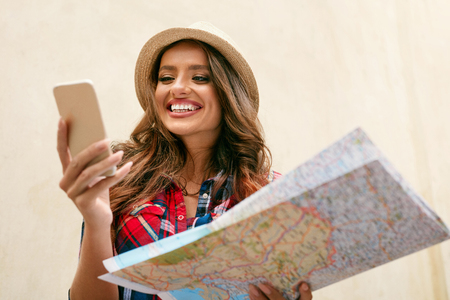 Woman Traveling. Beautiful Girl With Map And Phone Outdoors. Portrait Of Smiling Young Female Tourist Checking Location On Maps Using Phone Standing At Street. Travel Concept. High Resolution. 版權商用圖片