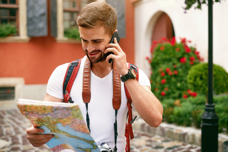 Young Tourist Male Talking On Phone While Walking On Street. Portrait Of Handsome Smiling Man In Stylish Clothes Using Smartphone On City Background. High Resolution.