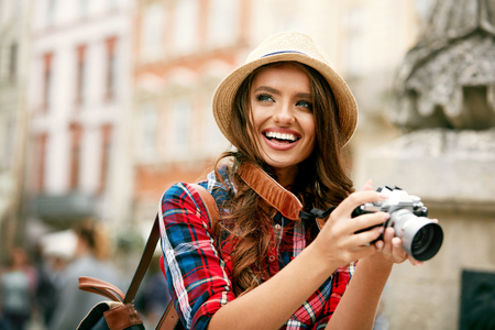 Tourist Woman With Camera Taking Photos Of Beautiful City Location. Portrait Of Happy Smiling Girl In Stylish Clothes And Hat With Photo Camera On Architecture Background. Travel concept