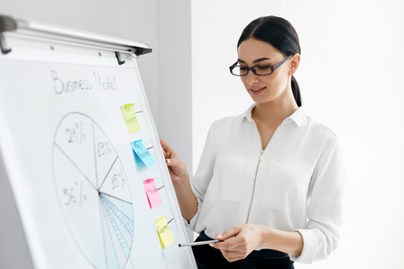 Présentation commerciale. Femme faisant une présentation à bord. Portrait de la belle travailleuse souriante en chemise blanche présentant des graphiques sur le tableau à feuilles mobiles travaillant dans le bureau. Haute résolution.