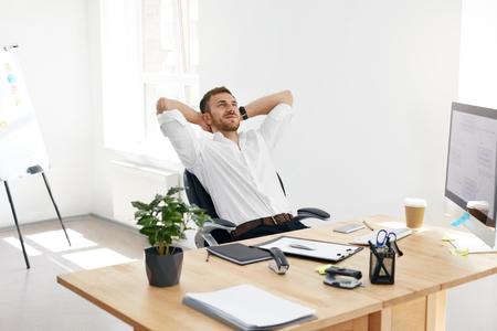 Trabajador relajante en la oficina. Hombre relajado en el trabajo. Retrato del hombre de negocios sonriente hermoso en la camisa blanca que descansa y que se relaja después de la sesión de trabajo en su escritorio del trabajo. Imagen de alta calidad.