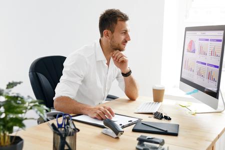 Młody Człowiek Biznesu Pracuje Na Komputerze W Biurze. Portret Przystojny Biznesmen W Białej Koszuli Siedzi Na Biurku Patrząc Na Monitor. Obraz wysokiej jakości.