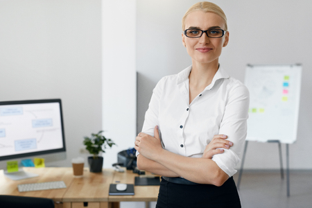 Business People. Portrait Of Woman In Office. Beautiful Smiling Woman In White Shirt Standing With Arms Crossed In Light Working Environment, Workplace. High Quality Image. Stock Photo