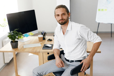 Man In Office. Portrait Of Male Worker In Formal Clothes Sitting At His Work Desk. Successful Confident Smiling Business Man In White Shirt Working In Light Workplace. High Quality Image.