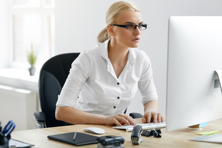 Business People. Woman Working On Computer In Office. Portrait Of Professional Beautiful Female Worker In Glasses And White Shirt Typing On Computer Keyboard Sitting At Work Desk. High Resolution.