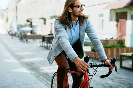 Cycle To Work. Stylish Male Cycling On Bicycle On Street. Portrait Of Handsome Young Smiling Man In Fashionable Mens Clothes Riding On Bike Outdoors. High Quality Image. Reklamní fotografie