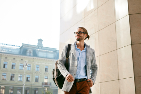 Men Style. Handsome Smiling Man On Street. Fashionable Male Wearing Glasses And Business Casual Mens Attire With Backpack Walking On Sunny City Street. Office And Work Fashion Clothes. High Quality Stock Photo