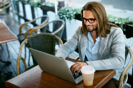 Man Working On Notebook From Cafe Outdoors. Portrait Of Stylish Successful Business Man In Modern Men Clothes Drinking Cup Of Hot Coffee While Working On Notebook Sitting At Table. High Quality Image. Stock Photo