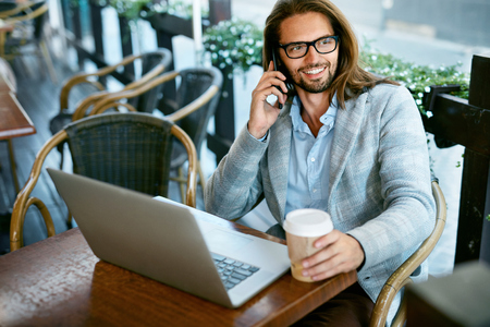 Work From Cafe. Man Talking On Phone Working In Cafe. Portrait Of Smiling Stylish Businessman Calling On Phone, Working On Notebook And Drinking Coffee From Paper Cup Outdoors. High Quality Image. Stock Photo