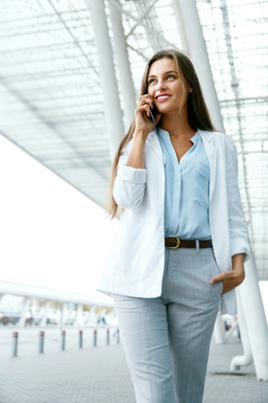 Beautiful Woman Talking On Phone Walking On Street. Portrait Of Stylish Smiling Business Woman In Fashionable Clothes Calling On Mobile Phone Near Office. Female Business Style. High Resolution.
