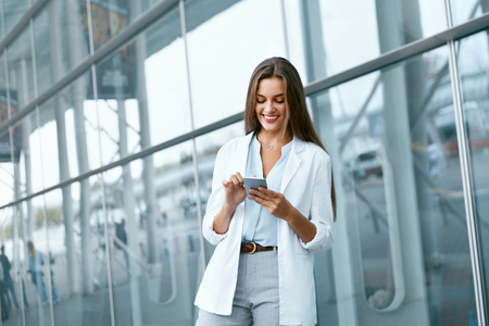 Business Woman With Phone On Street. Portrait Of Smiling Beautiful Young Female In Stylish Clothes Calling On Smartphone, Standing Near Office. High Quality Image. Stock Photo