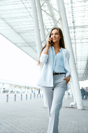 Beautiful Woman Talking On Phone Walking On Street. Portrait Of Stylish Smiling Business Woman In Fashionable Clothes Calling On Mobile Phone Near Office. Female Business Style. High Resolution. Stock Photo - 91946732