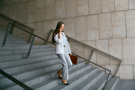 Business Women Style. Woman Going To Work Talking On Phone While Going Downstairs. Portrait Of Beautiful Smiling Female In Stylish Clothes Calling Someone While Going Down Stairs. High Resolution. Stock Photo