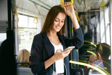 Woman Listening Music On Phone Riding In Bus. Portrait Of Stylish Smiling Girl Listening Music In Headphones, Using Smartphone While Riding In Public Transport. High Resolution.