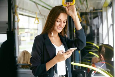 Femme, écoute, musique, téléphone, équitation, dans, autobus Portrait de l'élégante fille souriante écoutant de la musique au casque, utilisant un smartphone pendant la promenade dans les transports en commun. Haute résolution. Banque d'images - 91951355