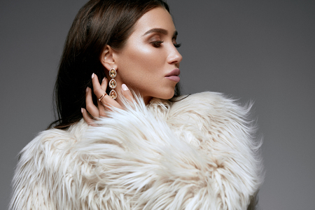 Winter Fashion Style. Beautiful Woman In Fur And Jewelry. Portrait Of Young Sexy Model With Beauty Makeup On Gorgeous Face In Luxury White Faux Fur Coat And Diamond Earrings. High Quality Image.
